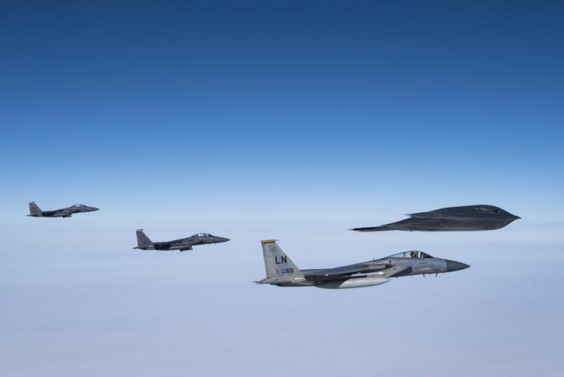 B-2 flies in formation with F-15C Eagles and F-15E Strike Eagles